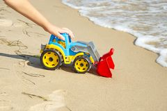 Children`s toy tractor on the sand at sea royalty free stock image