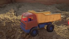 Children`s toy truck is in the sandbox close-up. 4K stock video