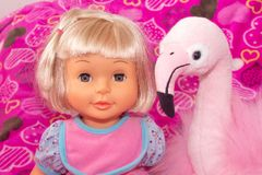 Children`s toys, baby doll and pink flamingo, gifts for children. Holiday with balloons. stock photo