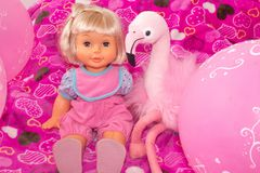 Children`s toys, baby doll and pink flamingo, gifts for children. Holiday with balloons. stock photography
