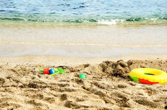 Children's toys on the beach close-up. Clear sea water. running wave Royalty Free Stock Photo
