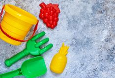 Children`s toys: bucket, shovel, rake on a stone background. Toys for the beach stock photos