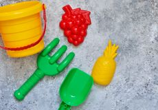 Children`s toys: bucket, shovel, rake on a stone background. Toy. Children`s toys: bucket, shovel, rake on a stone background royalty free stock photography