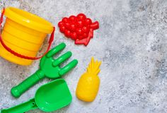 Children`s toys: bucket, shovel, rake on a stone background. Toys for the beach royalty free stock images