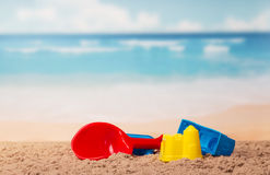 Children's toys castles and shovel in sand against sea. Stock Photo