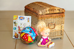 Children's toys and the container for their storage. Beautiful children's toys: doll, ball, book. Are located near the container for storage of toys Stock Photo