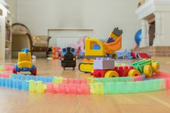 Children's toys on the floor. Close-up. Children's excavator, train and car. The children left behind a mess of toys in the livi stock photography