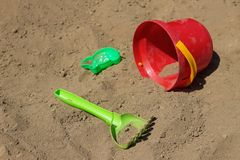 Children`s toys left on the sand, a bucket, a scraper and a mold for sculpting figures. Children`s toys left on the beach, a bucket, a scraper and a mold for stock photography