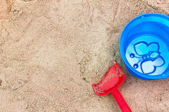 Children's toys in the sandbox. Red spade and blue bucket in the children's sandbox. View from above Stock Photography
