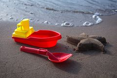 Ship and scoop - children`s toys and starfish made of sand. Sandy beach, sunny day royalty free stock images