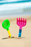 Children's toys stuck in the sand on the beach Royalty Free Stock Images