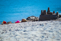 Children's toys and a tower of sand on the seashore. In Greece Royalty Free Stock Photography