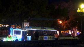 Children`s train rides on the quay at night stock video footage