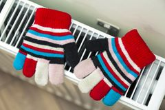 Children& x27;s warm hand knitted striped woolen gloves drying on hea. Ting radiator after winter day outside Royalty Free Stock Photos