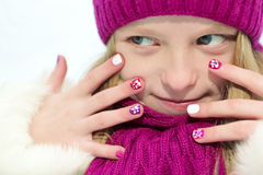 Children`s winter mixed colors manicure . Children`s winter mixed colors manicure with glitter under the snow the girl in the cherry hat and scarf on a white stock photo
