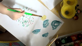Children`s and women`s hands paint the sun on a sheet of paper. A little girl draws a sun on a piece of paper over a tree with apples, her mother helps drawing stock video footage