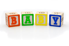 Children's wood blocks spelling the word baby over. Children's alphabet letters wood blocks spelling the word baby isolated over white background Royalty Free Stock Photos