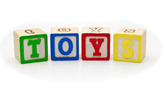 Children's wood blocks spelling the word toys over. Children's alphabet letters wood blocks spelling the word toys isolated over white background royalty free stock photo