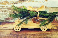 Children`s wooden car is lucky fir-tree branches against the background of an old vintage board. Wooden car carrying a christmas t Royalty Free Stock Photo