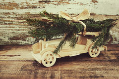 Children`s wooden car is lucky fir-tree branches against the background of an old vintage board. Wooden car carrying a christmas t Royalty Free Stock Images