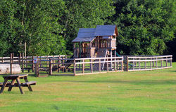Children's wooden play area. A wooden play area for children in a park. The structure of house is surrounded by a fence for security as the children play Royalty Free Stock Photo
