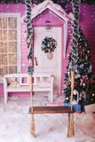 Children`s wooden swing on a rope in a New Year`s Eve, with a Christmas tree and toys in gentle tones. Children`s wooden swing on a rope in the New Year`s Stock Photos
