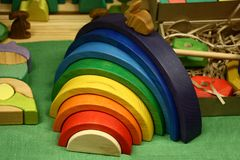Children`s wooden toys. Various wooden toys lie on a table. In the centre there is a cheerful rainbow stock images