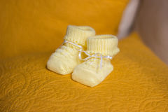 Children`s yellow bootees. On a yellow pillow Stock Image