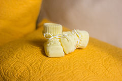 Children`s yellow bootees. On a yellow pillow Royalty Free Stock Photo