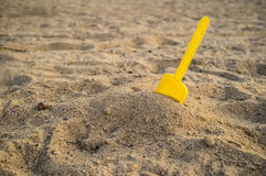 Children's yellow shovel on the beach Royalty Free Stock Image