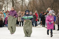 Children sack-racing during winter Maslenitsa carnival in Russia Royalty Free Stock Photography