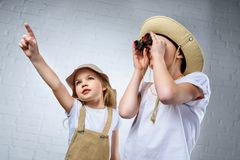Children in safari costumes and hats pointing and looking. In binoculars stock image