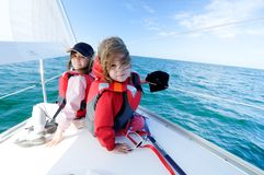 Children sailing on yacht. Two cute young girls sailing on yacht, blue sea in background Stock Photo