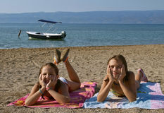 Children on sandy beach 2. Two young girls (sisters-best friends) lying down on the sandy beach smiling with head in hands stock image