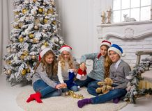 Children in Santa caps are decorate a Christmas tree in a room. Stock Images