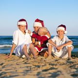 Children in santa claus hat are sitting on beach Royalty Free Stock Photo