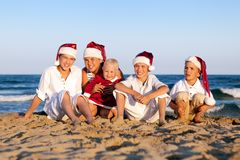 Children in santa claus hat are sitting on beach Royalty Free Stock Images