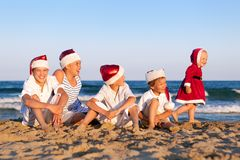 Children in santa claus hat are sitting on beach Stock Images