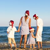 Children in santa claus hat are standing on beach Royalty Free Stock Photography