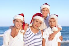 Children in santa claus hat are standing on beach Royalty Free Stock Photos