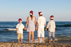 Children in santa claus hat are standing on beach Stock Images