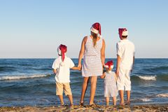 Children in santa claus hat are standing on beach Stock Photos