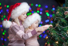 Children in Santa Claus hats near x-mas tree Stock Image