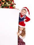 Children in Santa hat with banner . Children in Santa hat with banner near Christmas tree. Isolated Stock Image