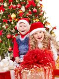Children in Santa hat with gift box . Children in Santa hat with gift box near Christmas tree. Isolated Stock Image