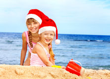 Children in santa hat playing on  beach. Royalty Free Stock Photo