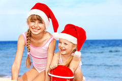 Children in santa hat playing on beach. Summer New Year Royalty Free Stock Photo