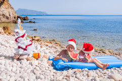 Children in Santa hats on the beach Stock Images