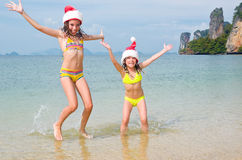 Children in santa hats having fun on beach. New year and christmas holiday concept Stock Photos