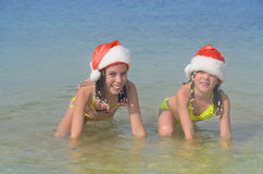 Children in santa hats having fun on beach Stock Image